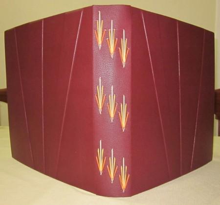 Álbum de fotografia com costura aparente em três cores e capa em pleno couro com relevos.