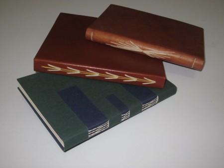 Encadernações contemporâneas com costura aparente em couro e em tecido.